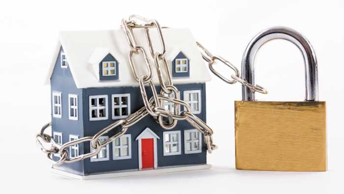 A house changed up with a padlock, indicating a mortgage prisoner.